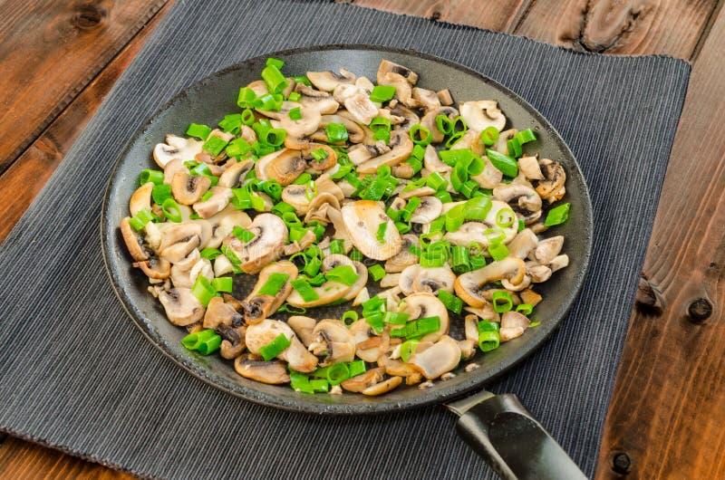 Τηγανισμένα μανιτάρια με το κρεμμύδι άνοιξη στο τηγάνι στοκ εικόνα με δικαίωμα ελεύθερης χρήσης