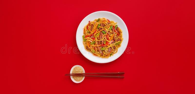 Τηγανισμένα νουντλς με το βόειο κρέας και τα λαχανικά Ασιατικά τρόφιμα Τοπ άποψη σχετικά με το κόκκινο υπόβαθρο στοκ εικόνες