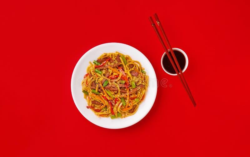 Τηγανισμένα νουντλς με το βόειο κρέας και τα λαχανικά Ασιατικά τρόφιμα Τοπ άποψη σχετικά με το κόκκινο υπόβαθρο στοκ φωτογραφία με δικαίωμα ελεύθερης χρήσης