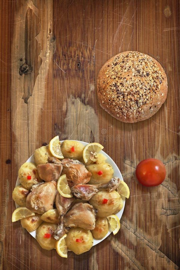 Τηγανισμένα πόδια κοτόπουλου με την ντομάτα πατατών και το ακέραιο ψωμί στο παλαιό ξύλο στοκ φωτογραφία