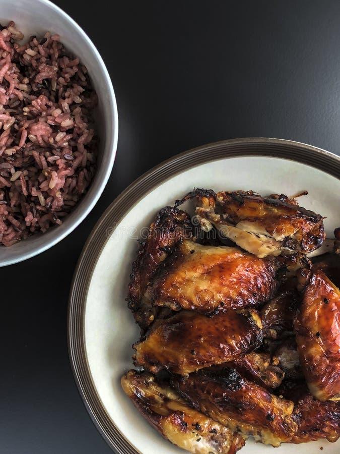 Τηγανισμένα τα αέρας φτερά κοτόπουλου στο κεραμικό πιάτο εξυπηρετούν με το μικρό κύπελλο του μαγειρευμένου μούρου ρυζιού Όλοι στη στοκ εικόνα με δικαίωμα ελεύθερης χρήσης