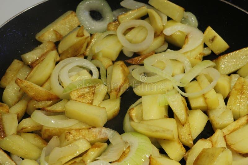 Τηγανισμένα τεμαχισμένα πατάτες και δαχτυλίδια κρεμμυδιών σε ένα τηγανίζοντας τηγάνι στοκ εικόνες με δικαίωμα ελεύθερης χρήσης