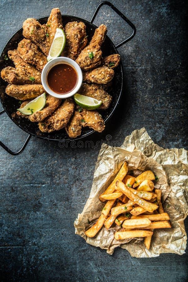 Τηγανισμένα τηγανητά ασβέστη και πατατών σάλτσας τσίλι φτερών κοτόπουλου στοκ φωτογραφία