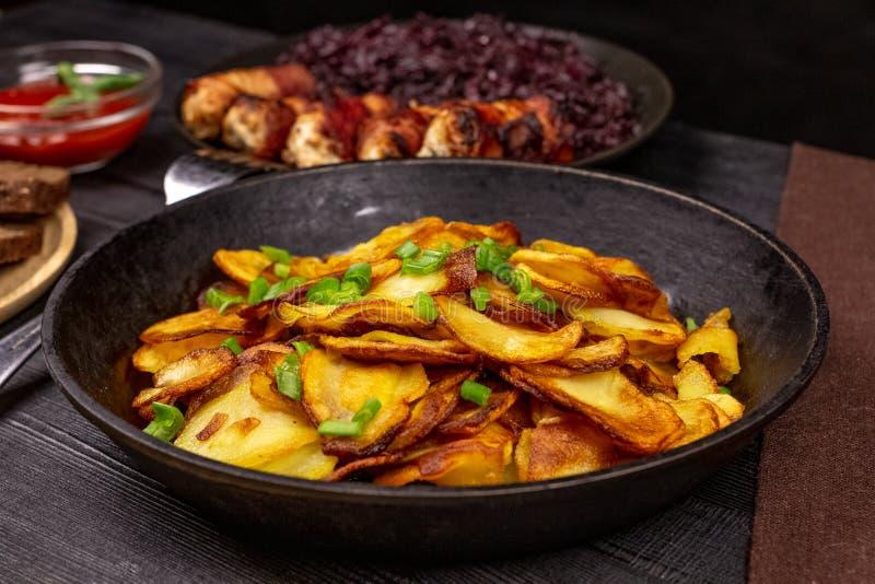 Τηγανισμένα τσιπ πατατών με τα πράσινα σε ένα δοχείο, μπροστά από τα σπιτικά λουκάνικα και το μαγειρευμένο λάχανο, σε ένα μαύρο α στοκ φωτογραφίες