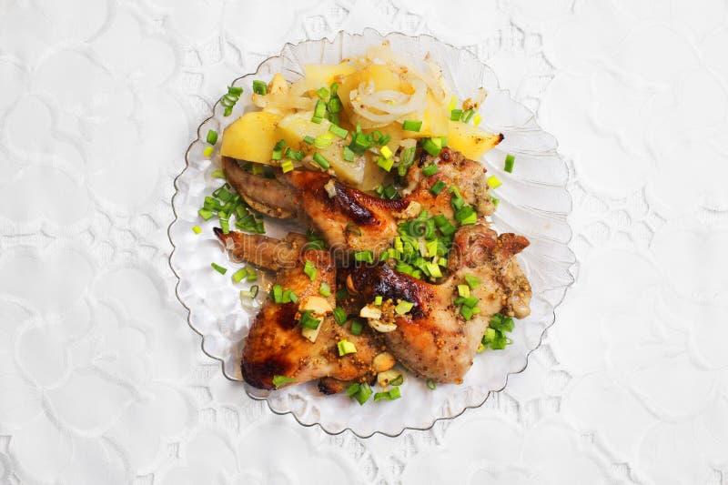 Τηγανισμένα φτερά κοτόπουλου με τα πράσινες κρεμμύδια και τις πατάτες στοκ εικόνες