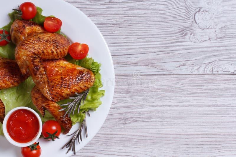 Τηγανισμένα φτερά κοτόπουλου με τη σάλτσα και τη τοπ άποψη λαχανικών στοκ εικόνες