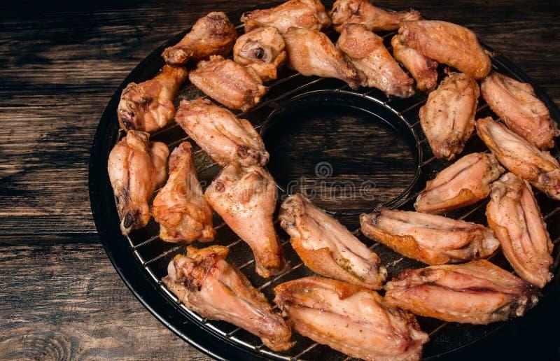 Τηγανισμένα φτερά κοτόπουλου σε μια σχάρα στοκ εικόνες