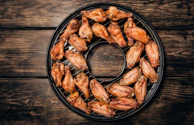Τηγανισμένα φτερά κοτόπουλου σε μια σχάρα στοκ φωτογραφία
