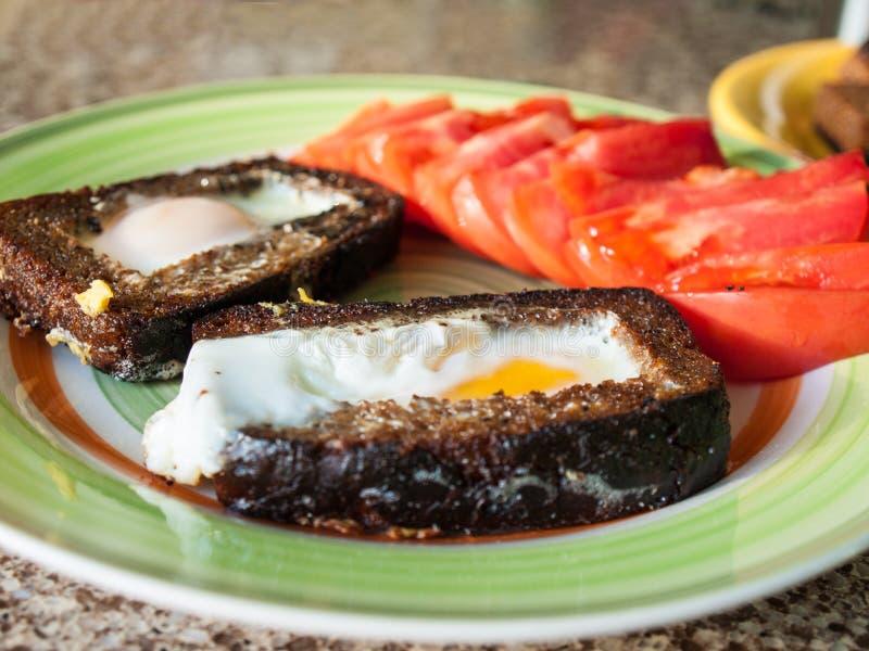 Τηγανισμένα croutons ψωμιού με τα αυγά και τις ντομάτες στοκ εικόνες