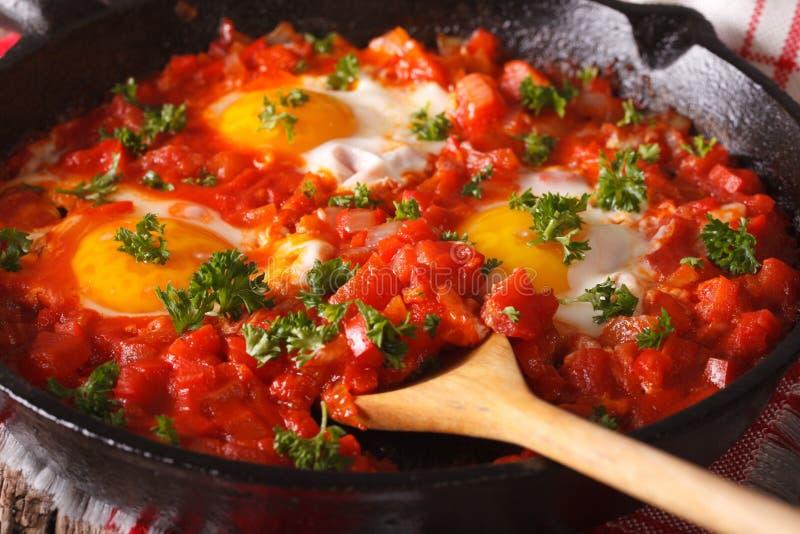 Τηγανισμένα Shakshuka αυγά με τη σάλτσα κοντά επάνω σε ένα τηγανίζοντας τηγάνι horizo στοκ φωτογραφία