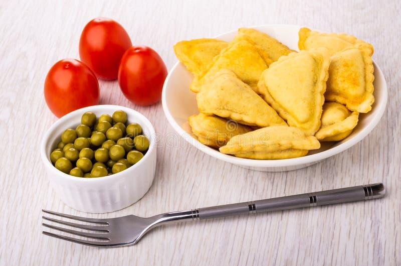 Τηγανισμένες αλμυρές πίτες στο πιάτο, δίκρανο, κύπελλο με τα πράσινα μπιζέλια, ντομάτες στον πίνακα στοκ φωτογραφίες