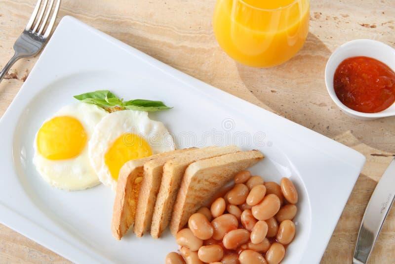 Τηγανισμένες αυγά, φασόλια και φρυγανιά σε ένα πιάτο με τη μαρμελάδα, το μέλι και το χυμό στοκ εικόνα