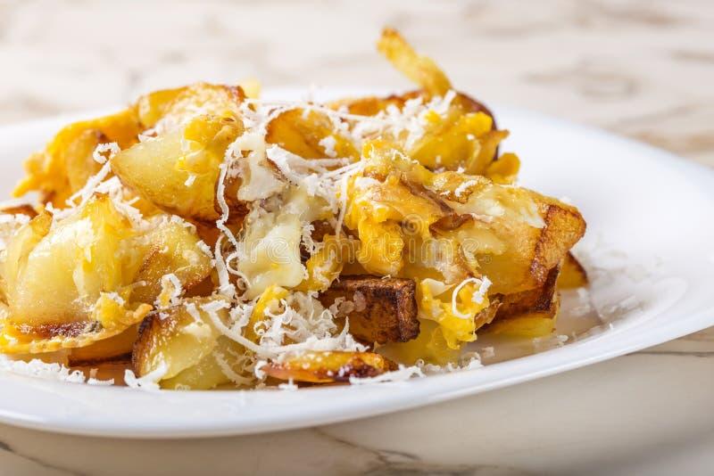 Τηγανισμένες πατάτες με τα ανακατωμένα αυγά και το τυρί παρμεζάνας στοκ εικόνες