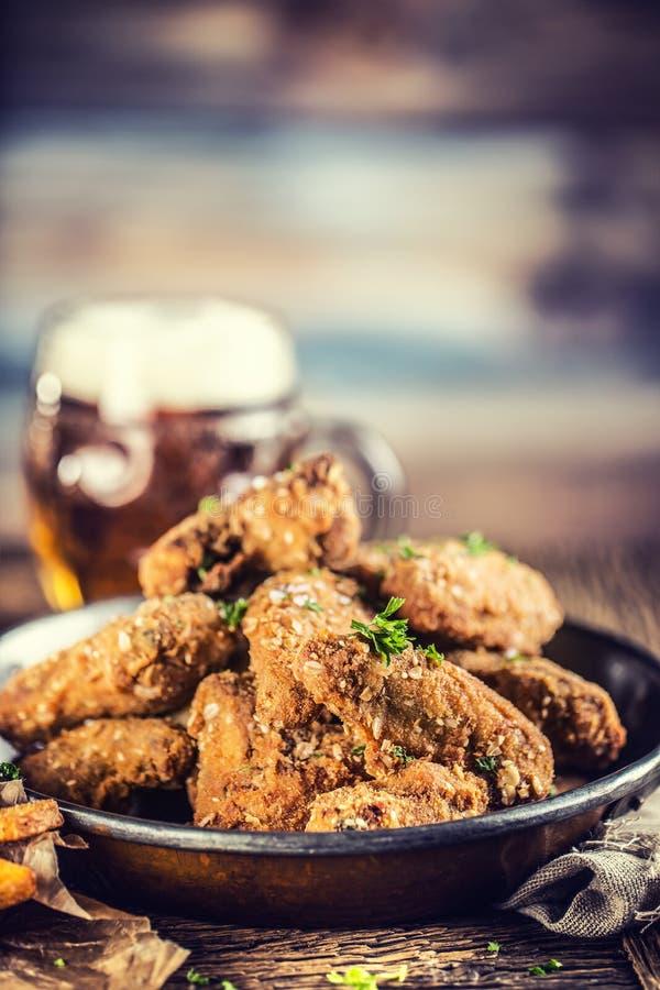 Τηγανισμένες τηγανητά φτερών κοτόπουλου και μπύρα σχεδίων στον πίνακα στοκ φωτογραφία με δικαίωμα ελεύθερης χρήσης