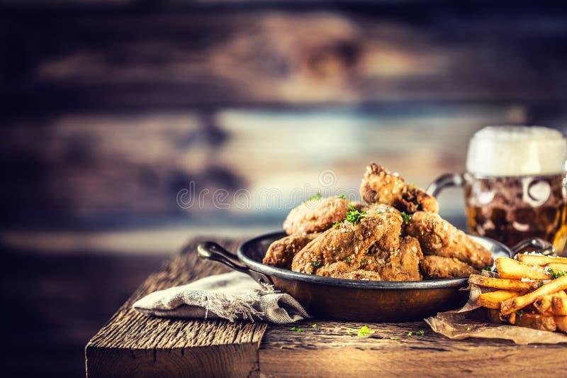 Τηγανισμένες τηγανητά φτερών κοτόπουλου και μπύρα σχεδίων στον πίνακα στοκ φωτογραφίες με δικαίωμα ελεύθερης χρήσης