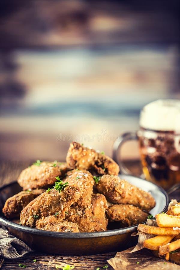 Τηγανισμένες τηγανητά φτερών κοτόπουλου και μπύρα σχεδίων στον πίνακα στοκ φωτογραφία