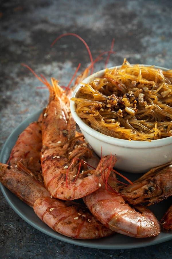 Τηγανισμένες ψημένες στη σχάρα γαρίδες με το νουντλς ρυζιού, σάλτσα, σκοτεινό υπόβαθρο στοκ φωτογραφίες