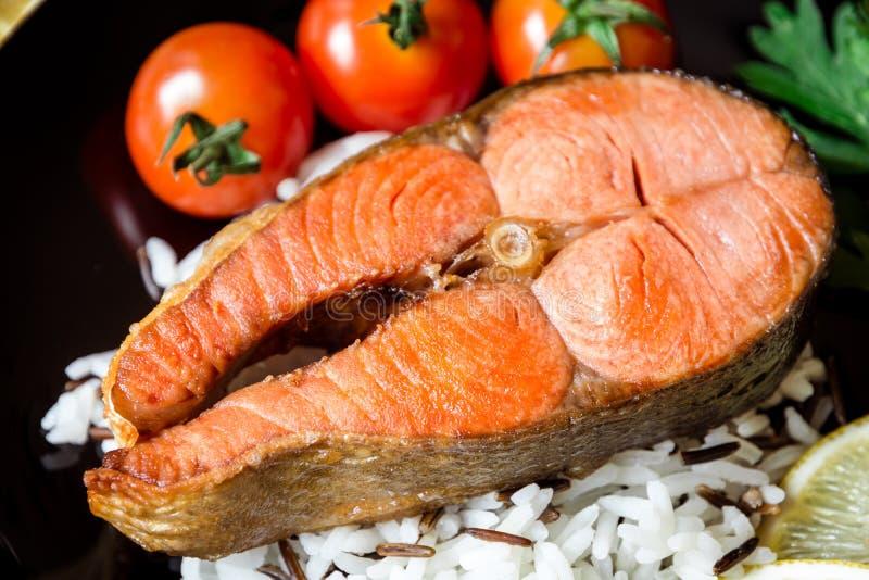 Τηγανισμένη μπριζόλα σολομών με τα λαχανικά και ρύζι στο πιάτο στοκ εικόνες