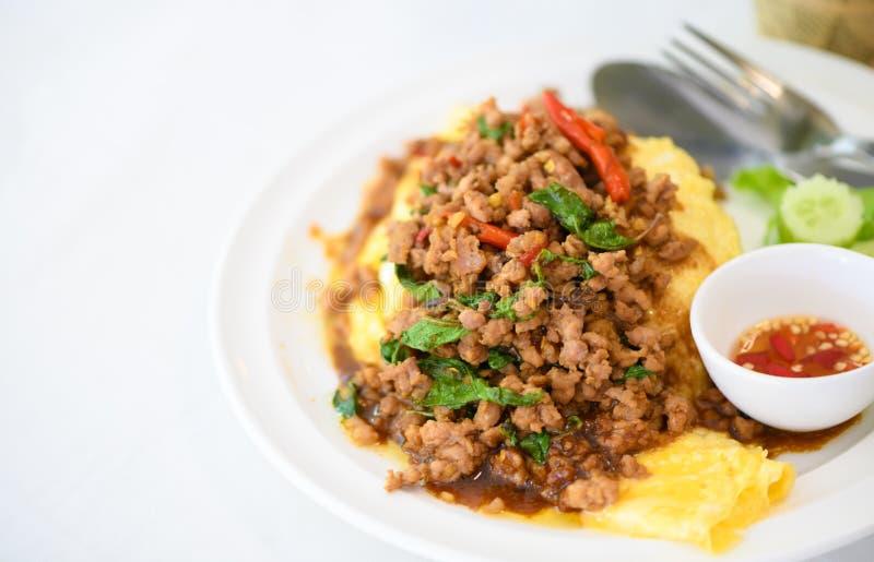 Τηγανισμένος βασιλικός με το χοιρινό κρέας σε μια σάλτσα ομελετών και ψαριών με τα τσίλι στοκ φωτογραφία