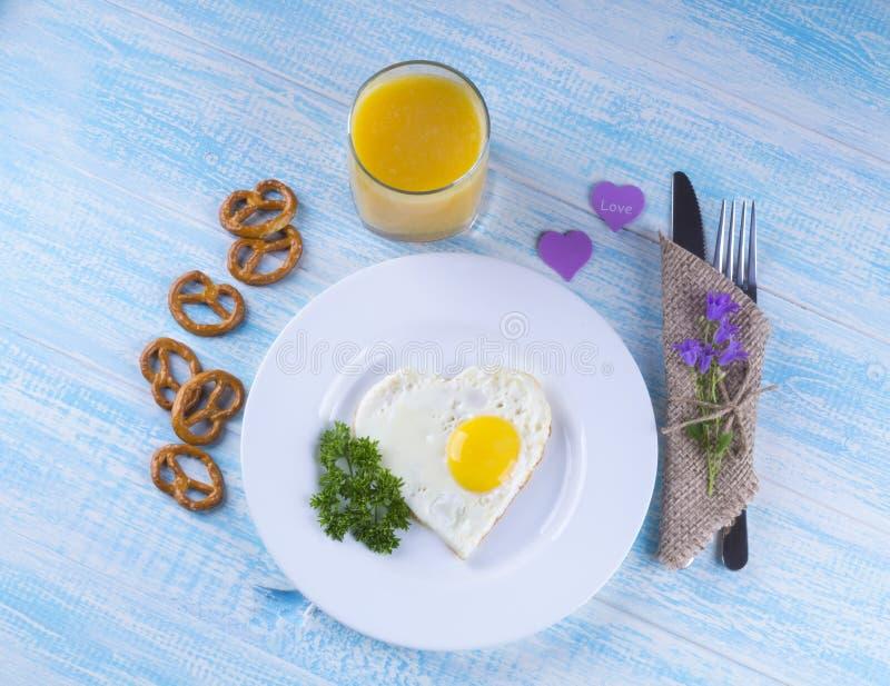 Τηγανισμένο αυγό με μορφή μιας καρδιάς, μια ανθοδέσμη των λουλουδιών, πρόσφατα στοκ εικόνες