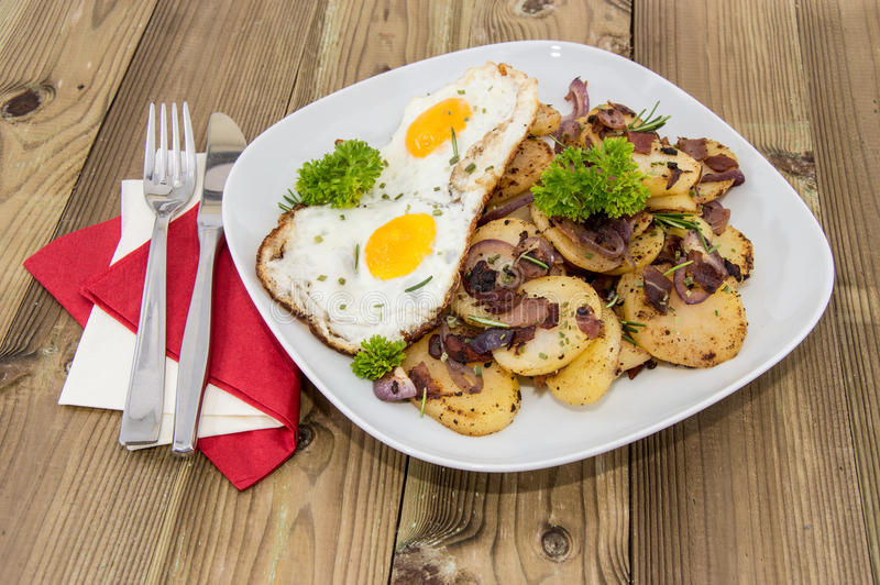 Τηγανισμένο αυγό σε έναν σωρό των ψημένων πατατών στοκ εικόνες με δικαίωμα ελεύθερης χρήσης