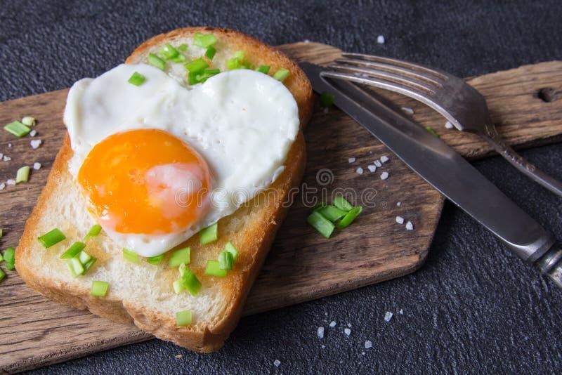 Τηγανισμένο αυγό σε μια φρυγανιά με ένα πράσινο κρεμμύδι βαλεντίνος ημέρας s στοκ φωτογραφία με δικαίωμα ελεύθερης χρήσης