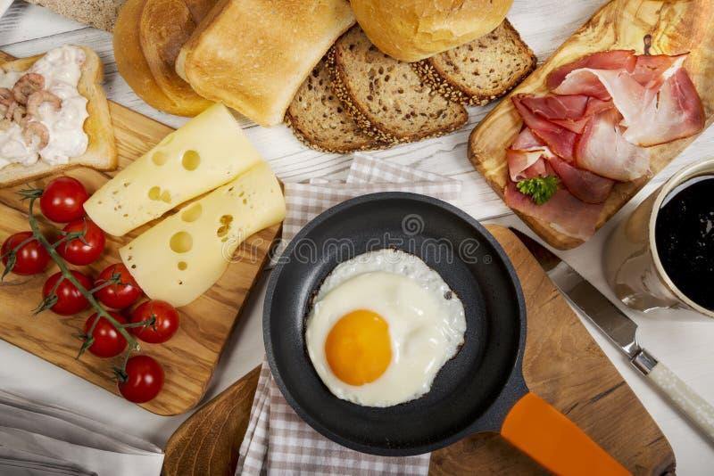 Τηγανισμένο αυγό στο τηγάνι, το τυρί, το ζαμπόν, το ψωμί και τα κουλούρια στοκ εικόνα