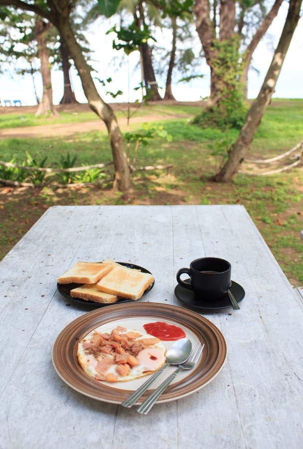 Τηγανισμένο αυγό, φρυγανιά ψωμιού μαρμελάδας φραουλών και μαύρο φλιτζάνι του καφέ στον άσπρο ξύλινο πίνακα στοκ εικόνες