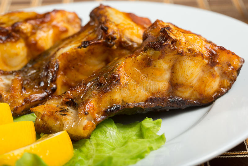 Τηγανισμένο γατόψαρο εύγευστα λιπαρά ψάρια σε ένα πιάτο στοκ εικόνες με δικαίωμα ελεύθερης χρήσης