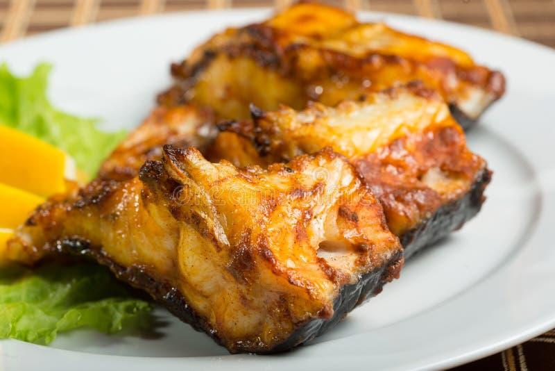 Τηγανισμένο γατόψαρο εύγευστα λιπαρά ψάρια σε ένα πιάτο στοκ φωτογραφίες