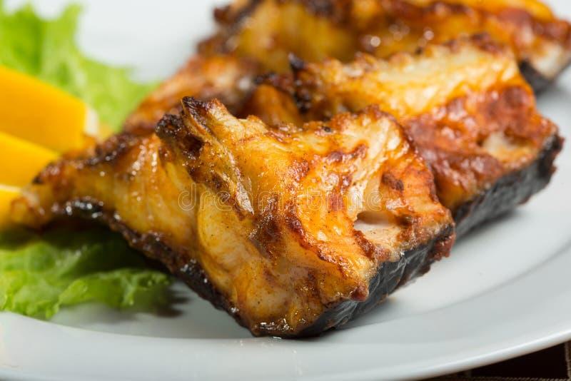 Τηγανισμένο γατόψαρο εύγευστα λιπαρά ψάρια σε ένα πιάτο στοκ φωτογραφία με δικαίωμα ελεύθερης χρήσης