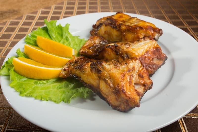 Τηγανισμένο γατόψαρο εύγευστα λιπαρά ψάρια σε ένα πιάτο στοκ εικόνα με δικαίωμα ελεύθερης χρήσης