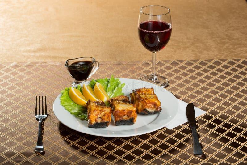 Τηγανισμένο γατόψαρο εύγευστα λιπαρά ψάρια σε ένα πιάτο στοκ εικόνες