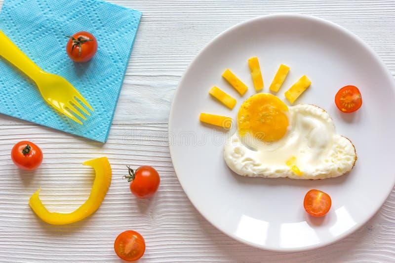 Τηγανισμένο ηλιοφάνεια πρόγευμα αυγών για το παιδί στο ξύλινο υπόβαθρο στοκ εικόνα