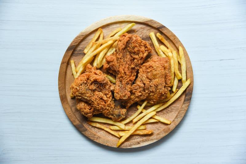 Τηγανισμένο κοτόπουλο τριζάτο στον ξύλινο δίσκο με τις τηγανιτές πατάτες να δειπνήσει στο επιτραπέζιο υπόβαθρο στοκ φωτογραφία με δικαίωμα ελεύθερης χρήσης