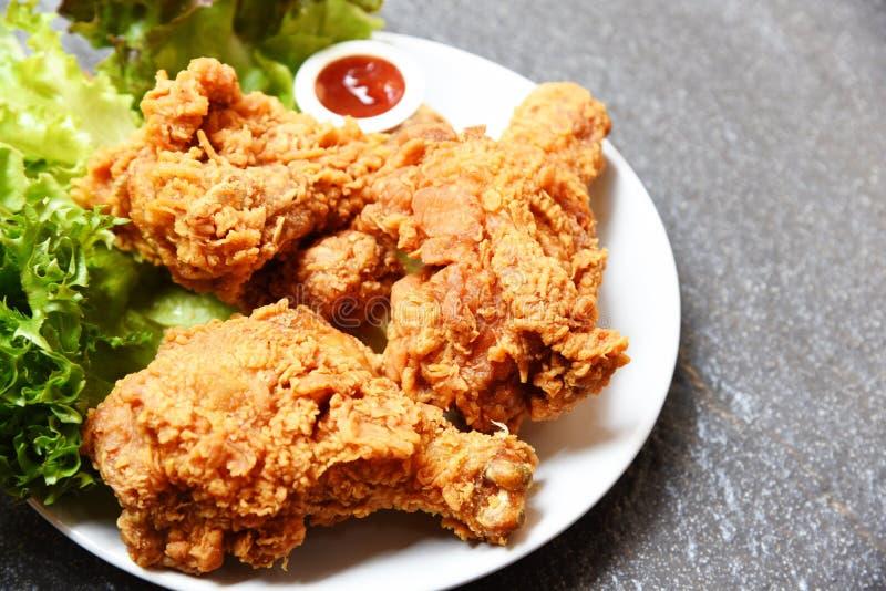 Τηγανισμένο κοτόπουλο τριζάτο στο άσπρο πιάτο με το λαχανικό μαρουλιού κέτσαπ και σαλάτας στο σκοτεινό πιάτο στοκ εικόνα