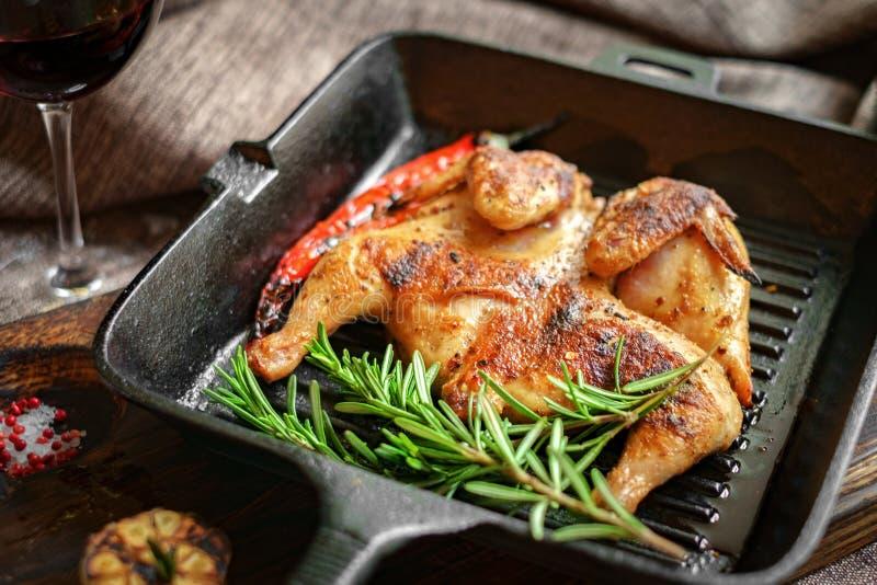 Τηγανισμένο κοτόπουλο ψητού σε ένα τηγανίζοντας τηγάνι σε έναν ξύλινο πίνακα στοκ φωτογραφία