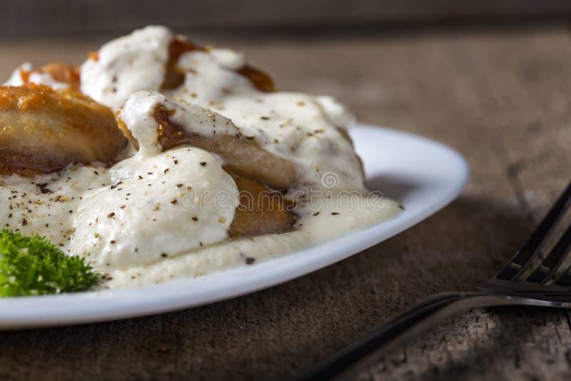 Τηγανισμένο κοτόπουλο με την ξινή κρέμα και καρυκεύματα στο πιάτο πέρα από το ξύλο στοκ εικόνες