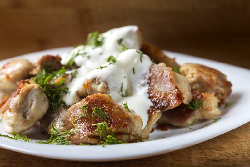 Τηγανισμένο κρέας κοτόπουλου με την ξινή κρέμα και άνηθος στο πιάτο στοκ εικόνα