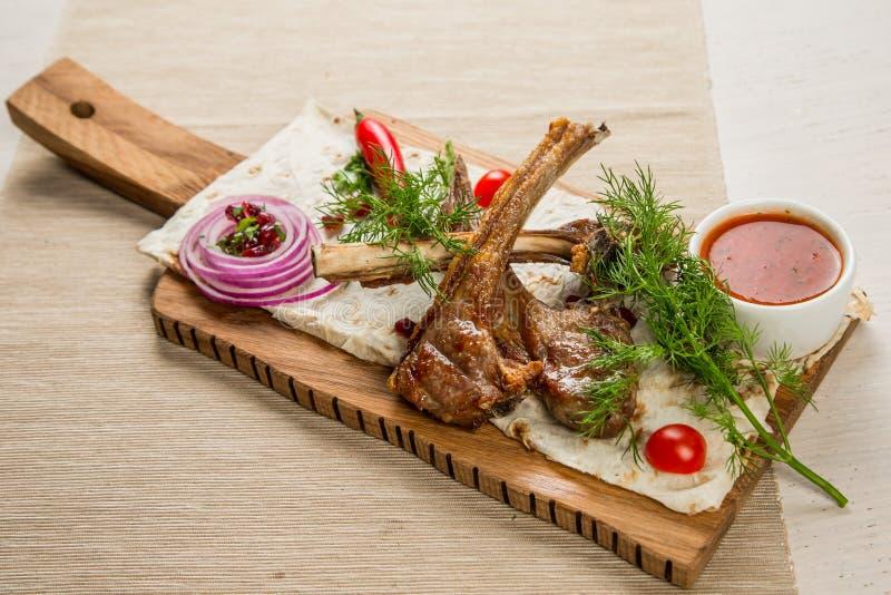 Τηγανισμένο κρέας με τα λαχανικά και τις σάλτσες σε έναν ξύλινο πίνακα στοκ φωτογραφίες με δικαίωμα ελεύθερης χρήσης