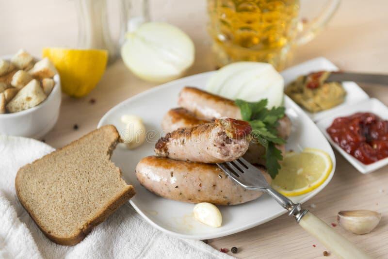 Τηγανισμένο λουκάνικο με το κέτσαπ και μουστάρδα σε ένα δίκρανο, ένα κομμάτι του ψωμιού, λουκάνικα χοιρινού κρέατος κρέατος σε έν στοκ εικόνες