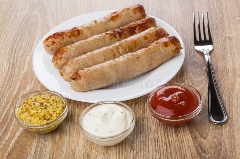 Τηγανισμένο λουκάνικο στο πιάτο, το κέτσαπ, τη μαγιονέζα, τη μουστάρδα και το δίκρανο στοκ φωτογραφίες με δικαίωμα ελεύθερης χρήσης