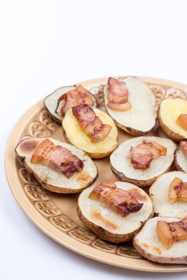 Τηγανισμένο μπέϊκον στις ψημένες πατάτες με το διάστημα αντιγράφων στοκ εικόνα
