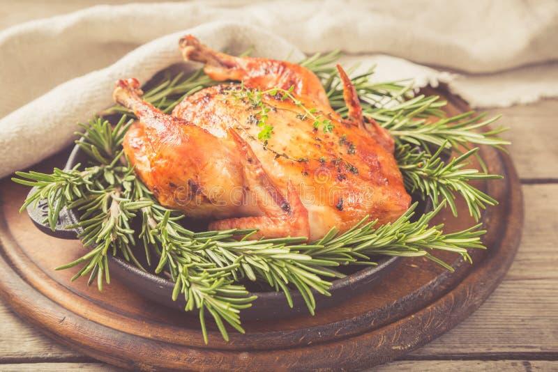 Τηγανισμένο ολόκληρο κοτόπουλο με τα χορτάρια πέρα από το φυσικό ξύλινο υπόβαθρο ποιοι στοκ εικόνες