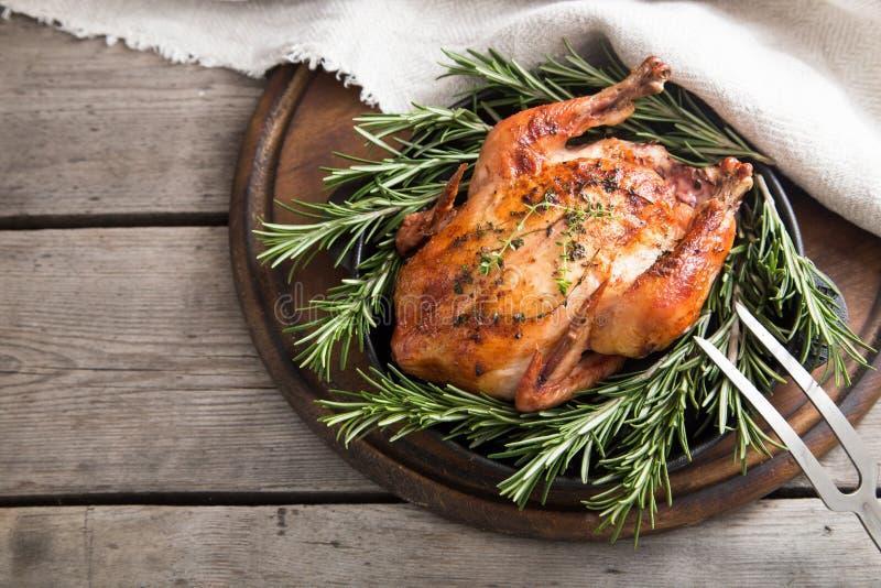 Τηγανισμένο ολόκληρο κοτόπουλο με τα χορτάρια πέρα από το φυσικό ξύλινο υπόβαθρο ποιοι στοκ φωτογραφίες