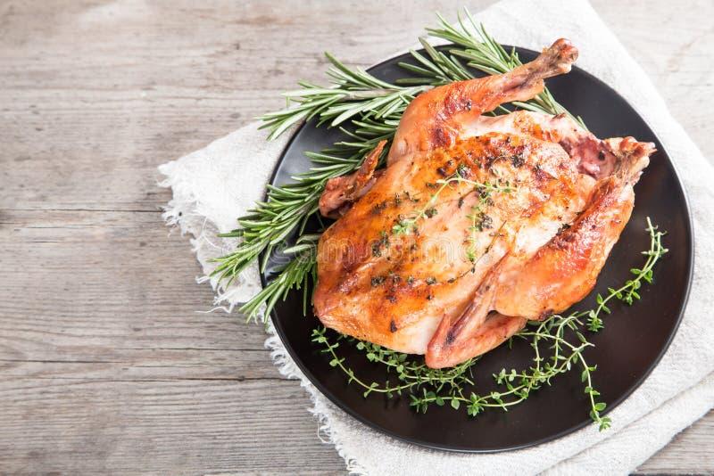 Τηγανισμένο ολόκληρο κοτόπουλο με τα χορτάρια πέρα από το φυσικό ξύλινο υπόβαθρο ποιοι στοκ εικόνες με δικαίωμα ελεύθερης χρήσης