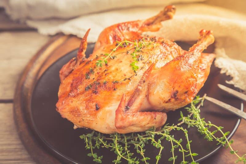 Τηγανισμένο ολόκληρο κοτόπουλο με τα χορτάρια πέρα από το φυσικό ξύλινο υπόβαθρο ποιοι στοκ φωτογραφία με δικαίωμα ελεύθερης χρήσης