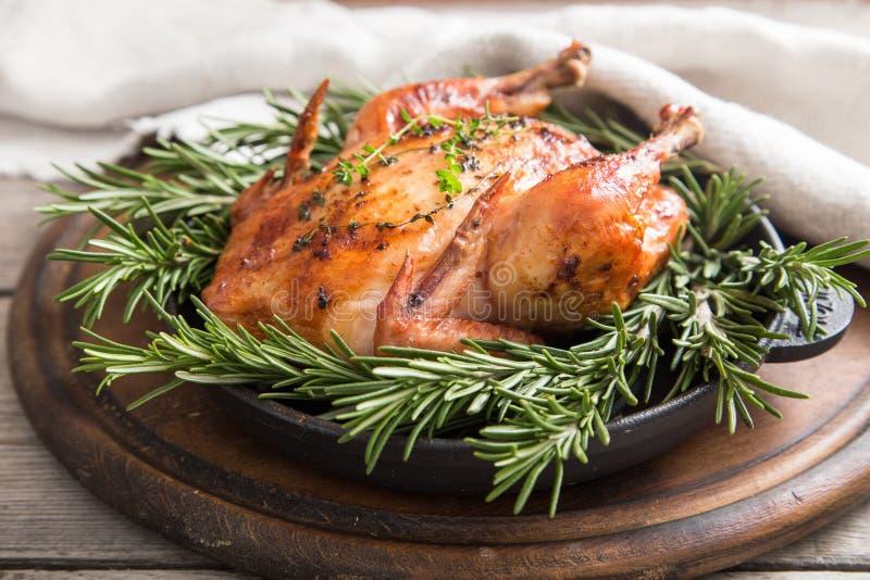 Τηγανισμένο ολόκληρο κοτόπουλο με τα χορτάρια πέρα από το φυσικό ξύλινο υπόβαθρο ποιοι στοκ εικόνα