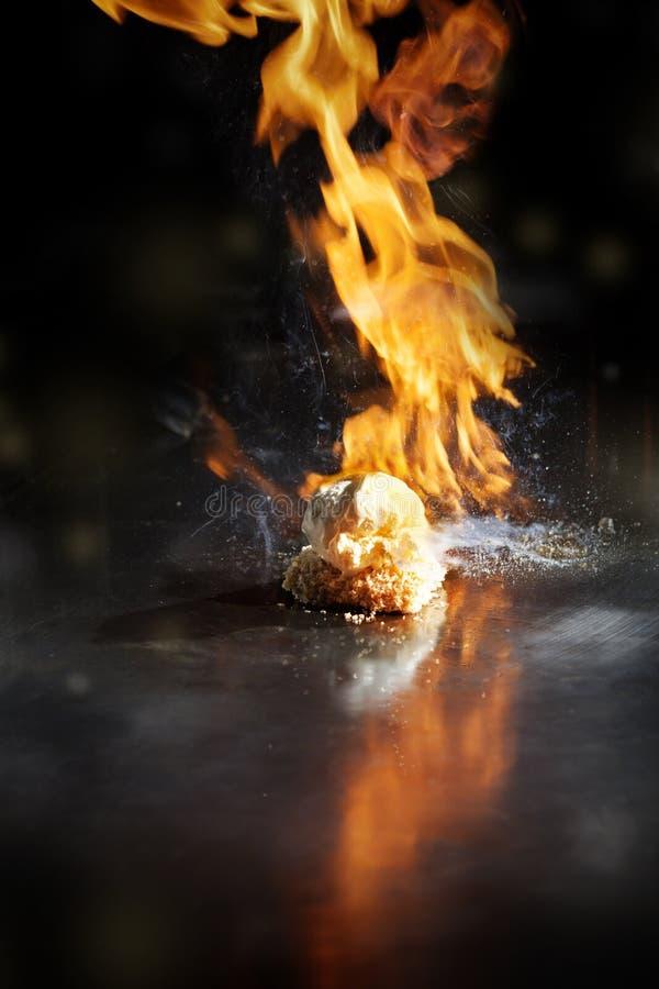 Τηγανισμένο παγωτό σε ένα καυτό τηγάνι που δίνει έξω την πυρκαγιά στοκ φωτογραφία