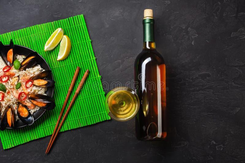 Τηγανισμένο ρύζι με τα μύδια θαλασσινών, γαρίδες, βασιλικός σε ένα μαύρο πιάτο με το μπουκάλι κρασιού, wineglass, λεμόνι, chopsti στοκ φωτογραφίες με δικαίωμα ελεύθερης χρήσης